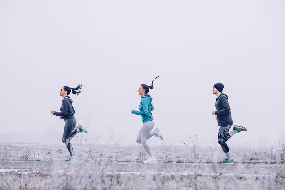 Three athletic people running outdoors in the winter on an open road