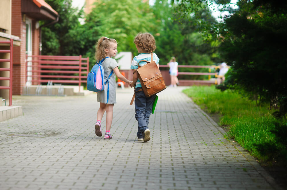 Boy and girl hand in hand with school bags behind the back.