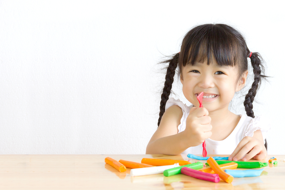kid playing with playdough