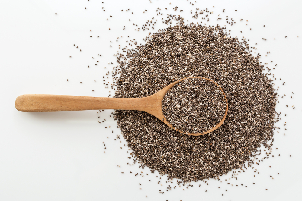 chia seeds in wooden spoon on white background