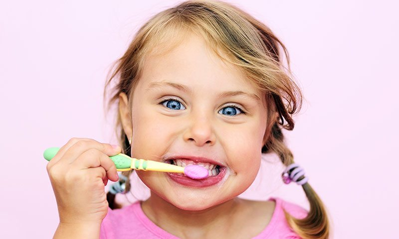 kid brushing teeth facing camera on pink background