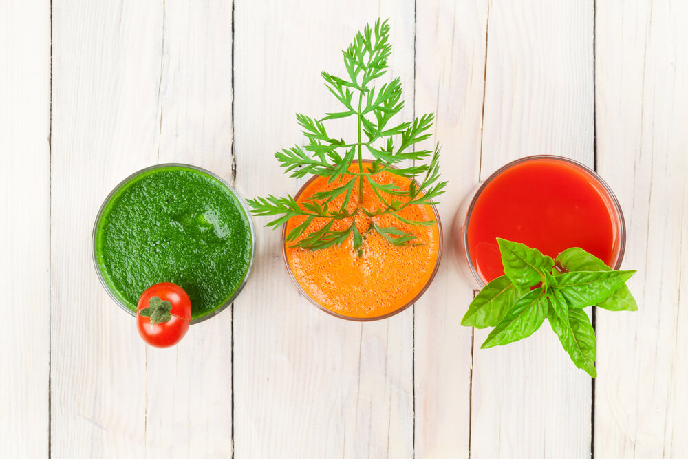 top view of 3 fresh vegetable smoothies on wooden table