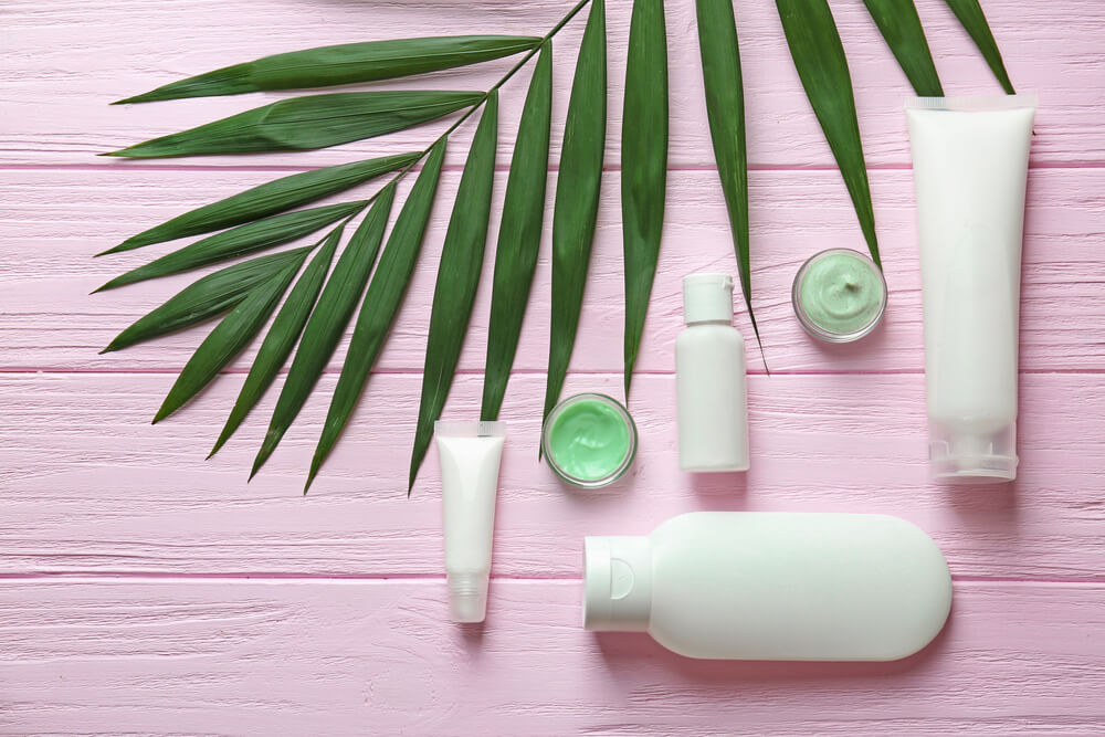 moisturizer bottles with green leaf on pink wooden background