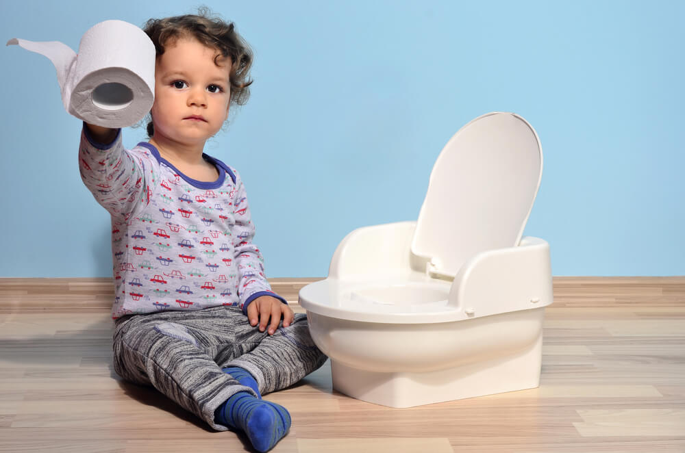 Baby toddler sitting on the floor near a potty and playing with toilet paper