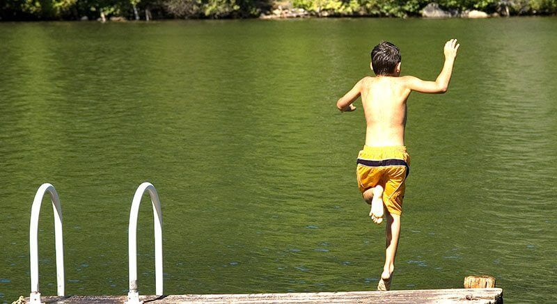boy jump off dock into lake
