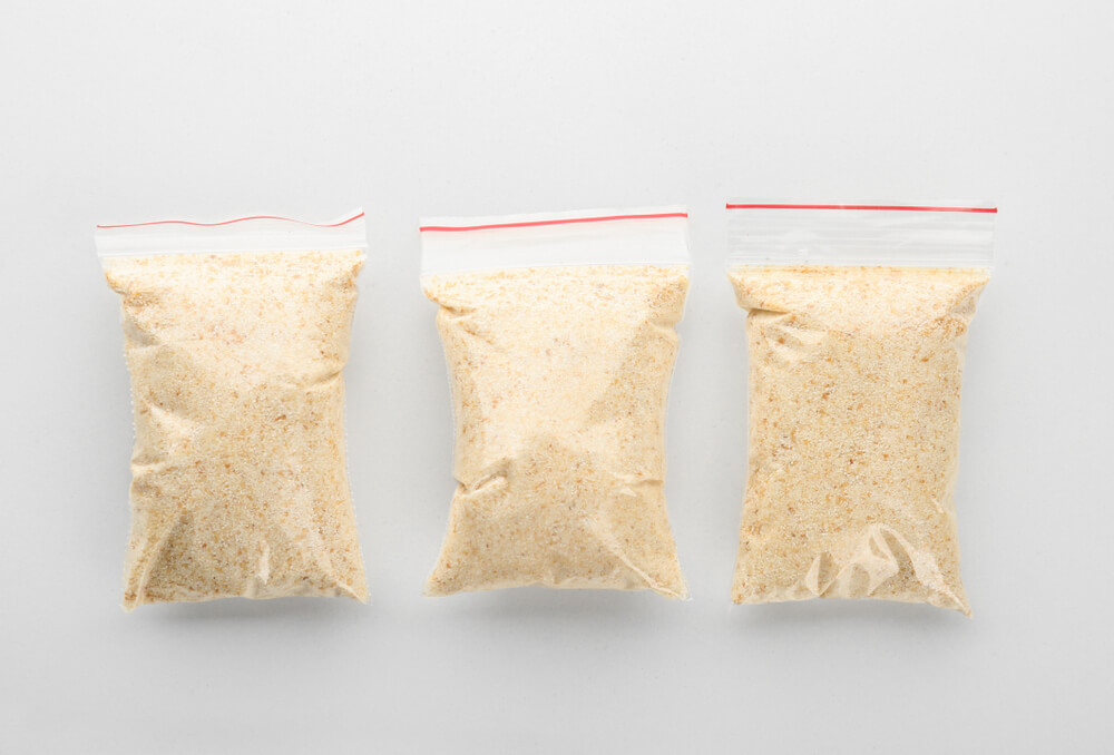 Ziploc bags filled with dried garlic powder on white background