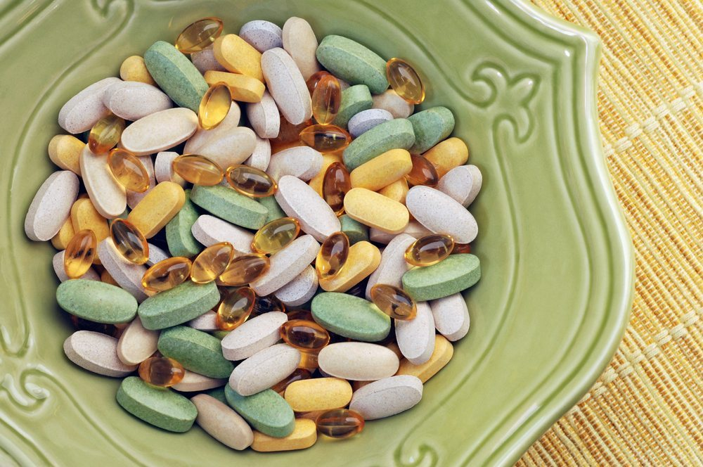 top view of a green bowl of various colourful pills on straw placemat