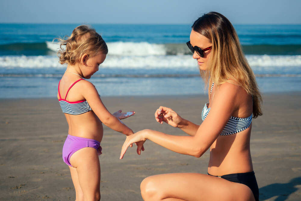 mother smears on her daughter sunscreen on the beach