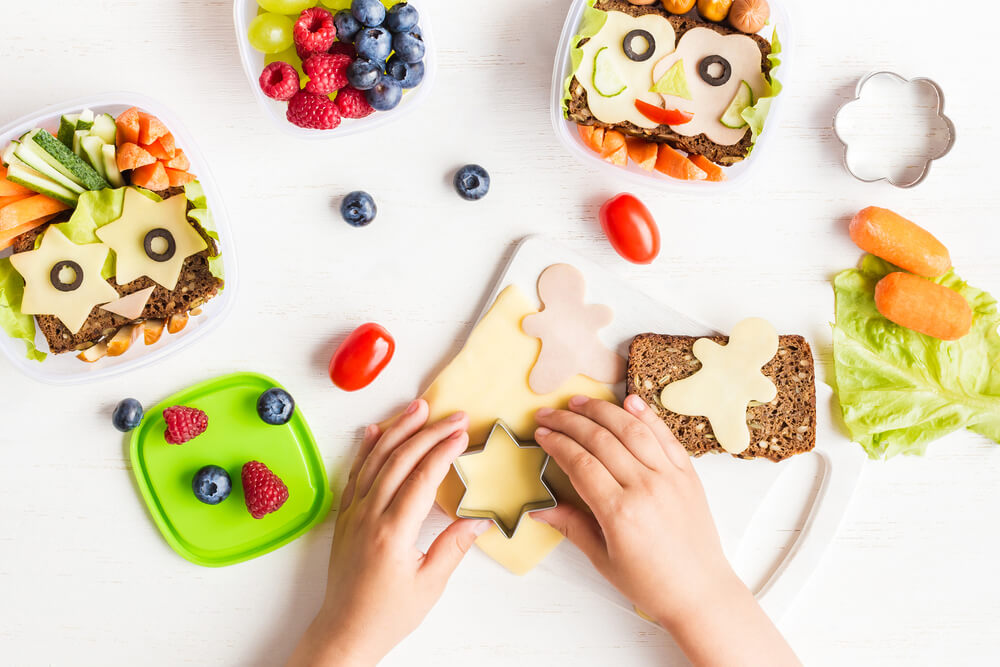 top view of kid's hands making school lunches