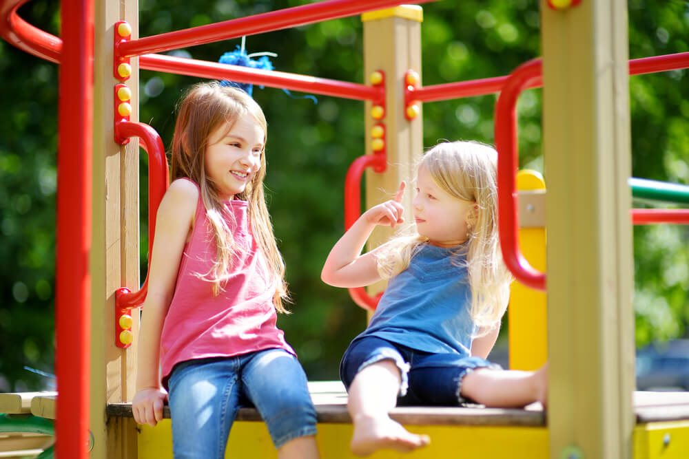 Two little girls having fun on a playground outdoors in summer