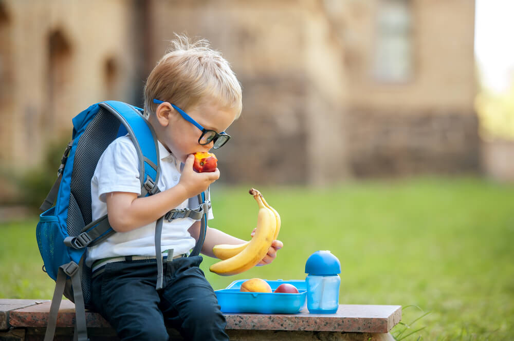 Cute schoolboy eating outdoors the school from plastic lunch box