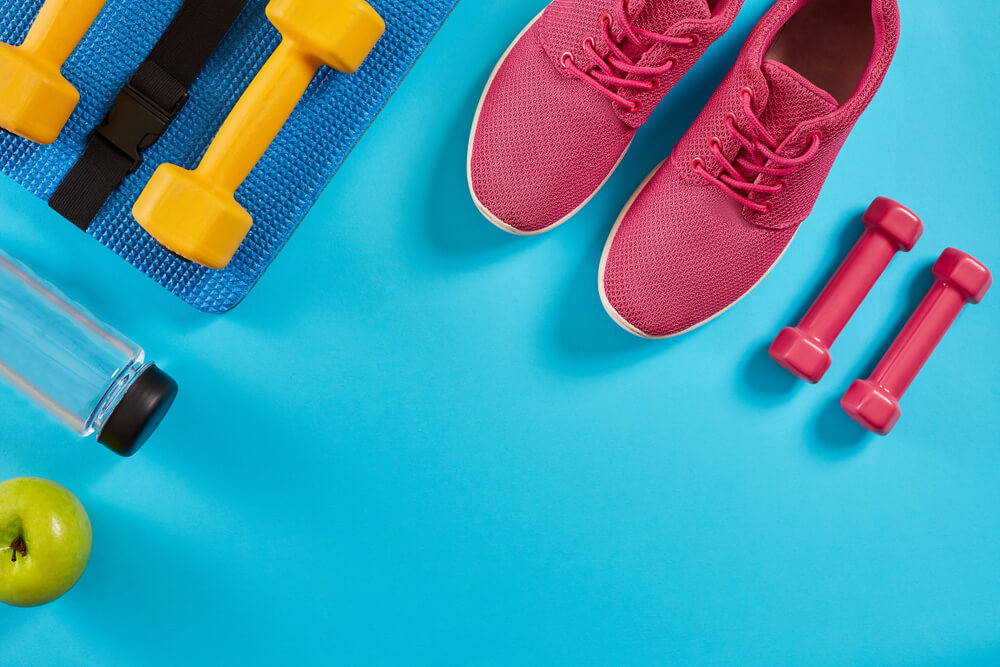 Female running shoes, dumbbells, and bottle of water on bright blue background