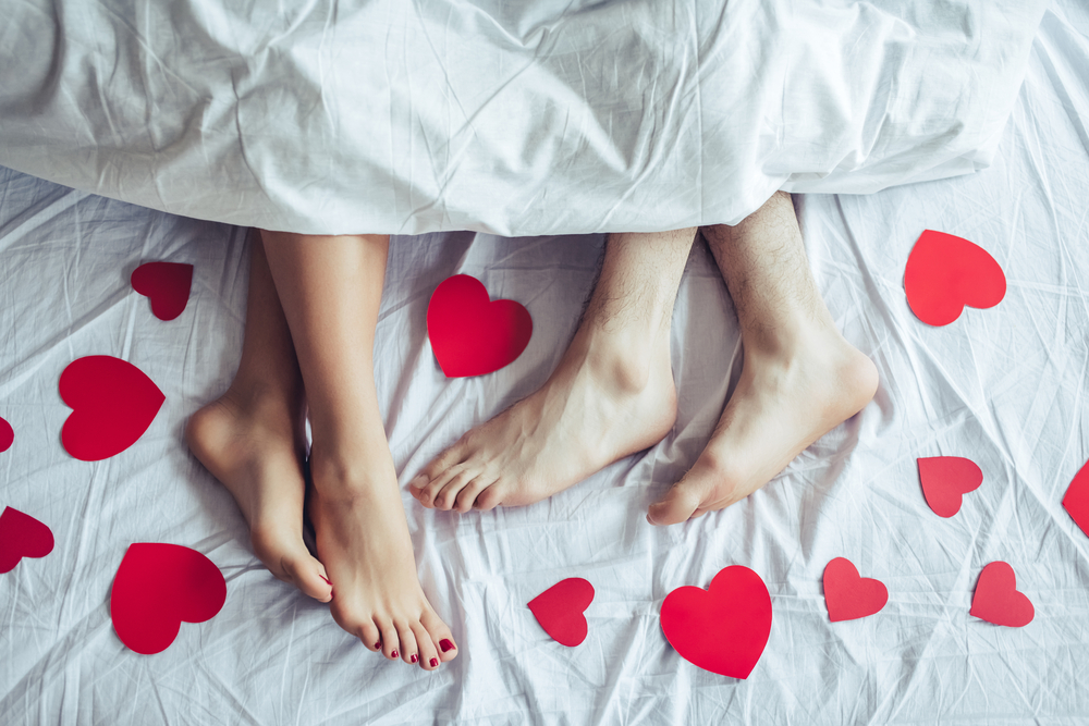 Close up of male and female feet in bed under blanket covered by small red paper hearts