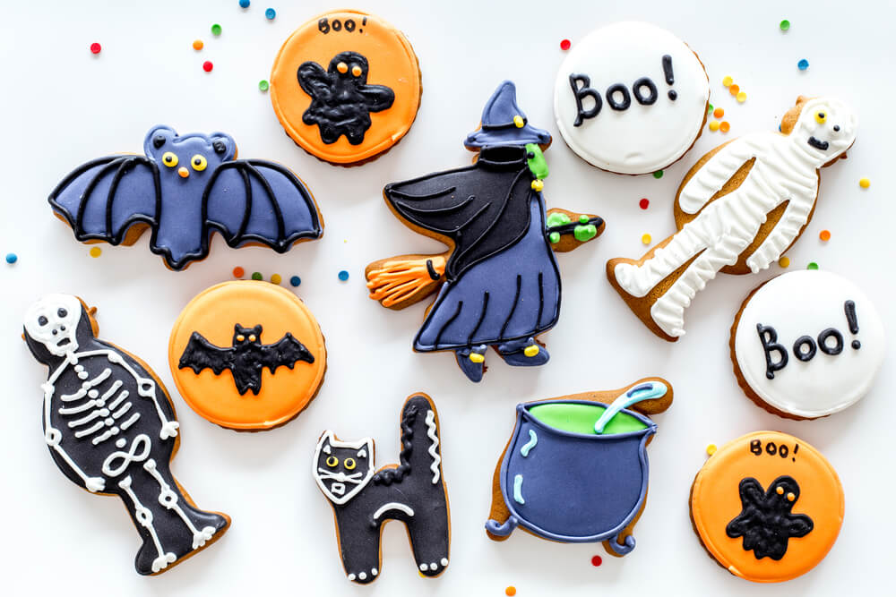 Bright halloween gingerbread cookies background with bat, witch, skeleton, ghost on white background top view