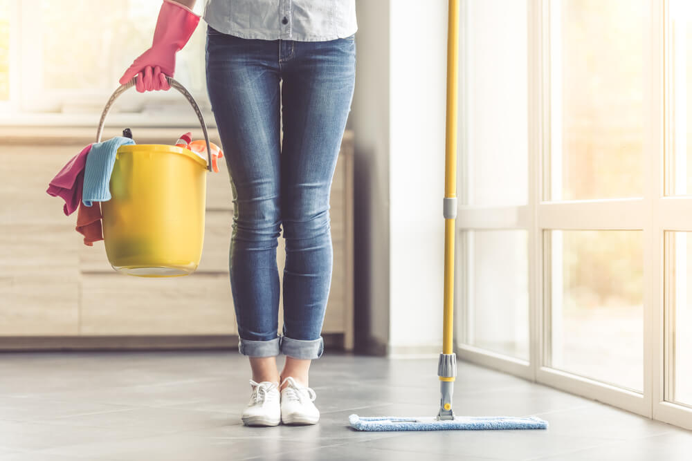 Cropped image of woman in protective gloves holding a flat wet-mop and bucket with detergents and rags while cleaning her house