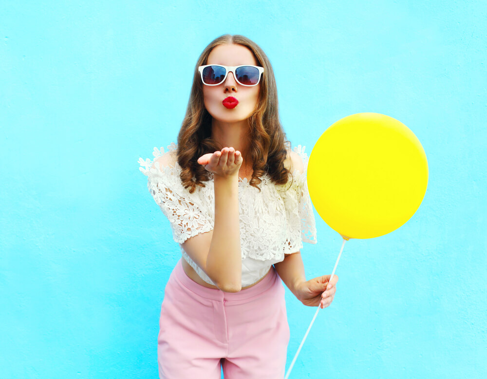 Pretty young woman in sunglasses with air balloon sends an air kiss over colorful blue background
