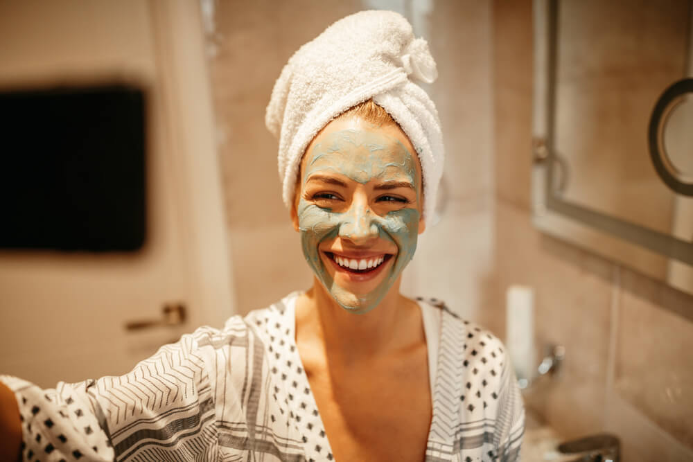 woman laughing in bathroom with clay mask on face and hair wrapped in a towel