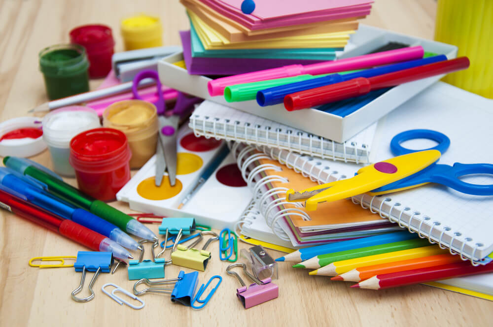 pile of school supplies on light wood table