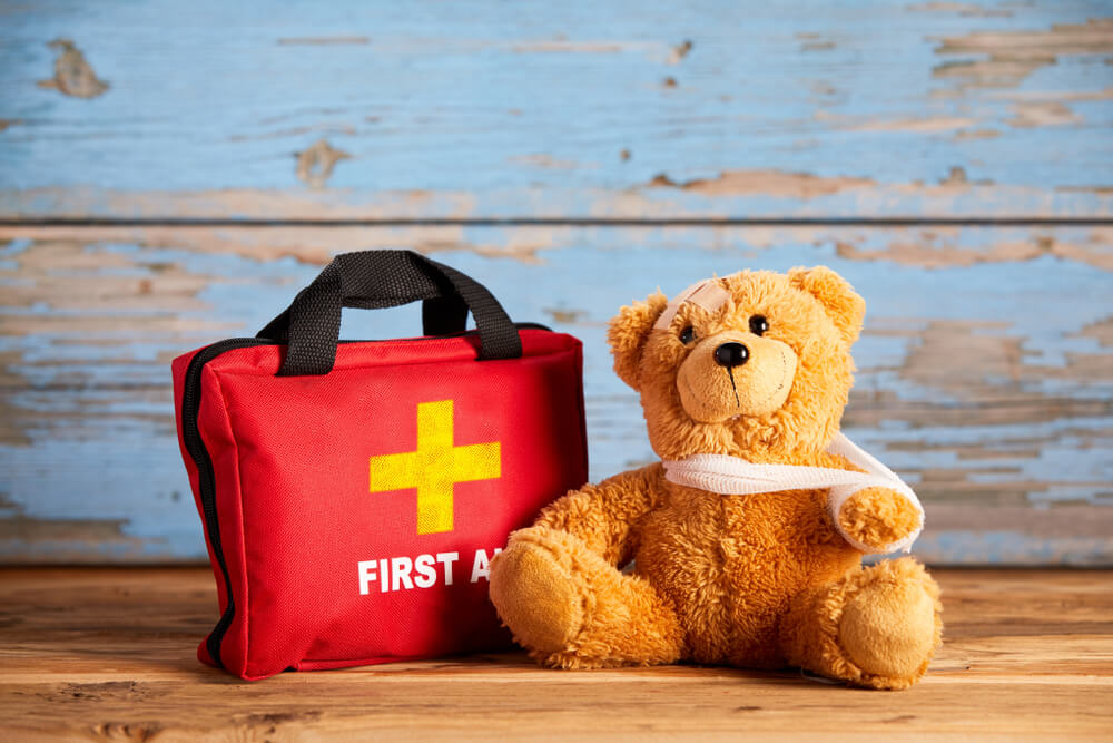 Little teddy bear with an injured arm in a sling sitting alongside a red first aid bag on rustic wood