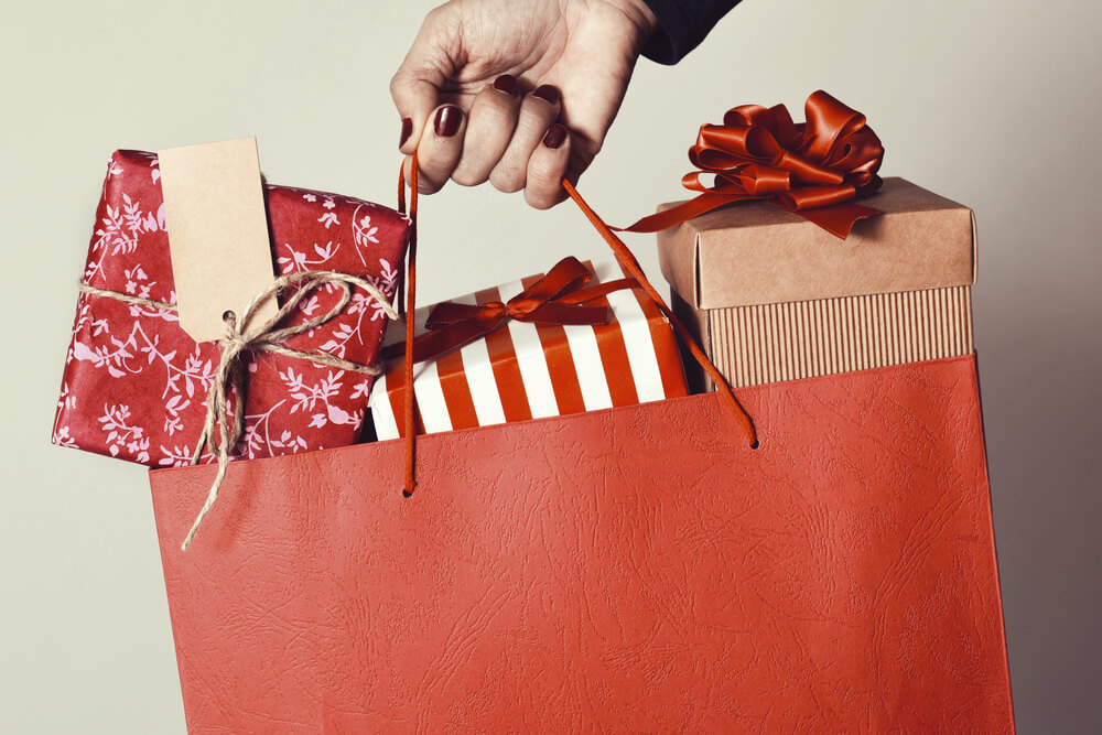 closeup of the hand of a young woman with her fingernails painted red holding a red shopping bag full of gifts wrapped in different papers