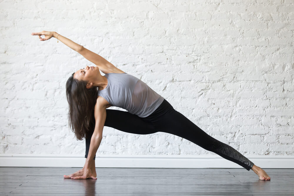 Young woman practicing yoga in extended side angle pose