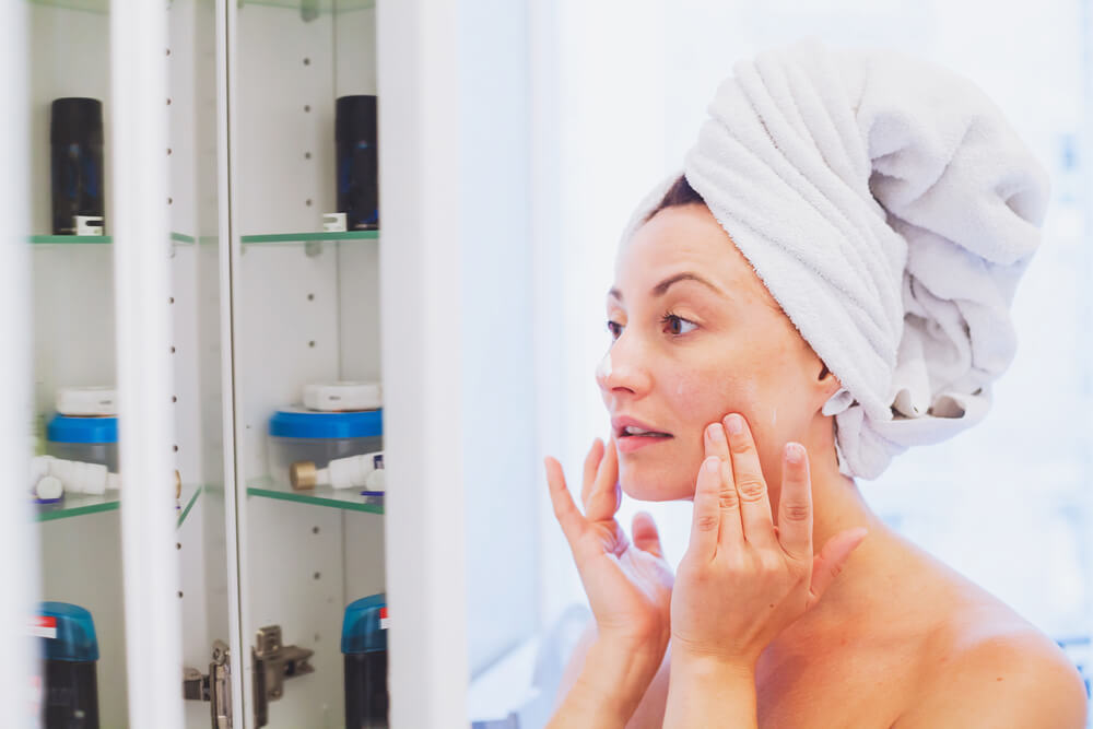 middle aged woman applying moisturising cream on her face after shower in bathroom in front of the mirror