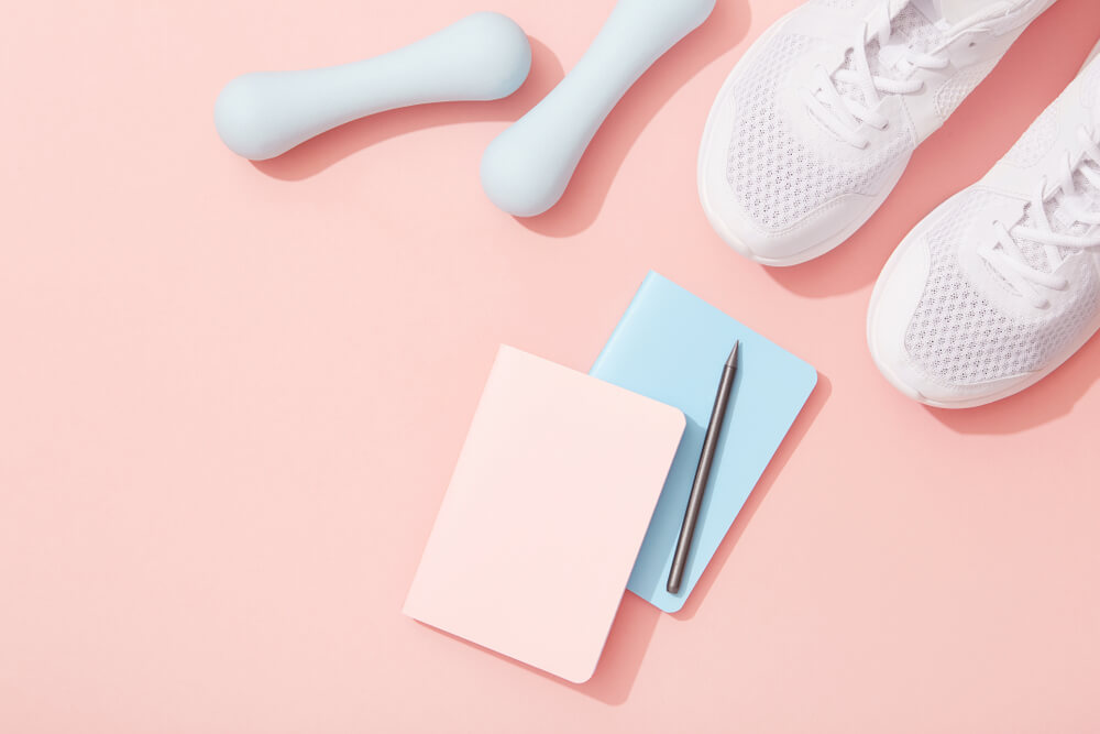Female sports flat lay, dumbbells, notepad, sneakers on pink background