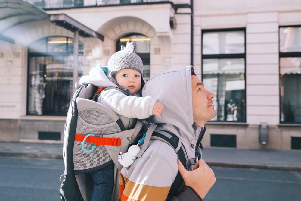 Father with child son in carrier backpack on city street