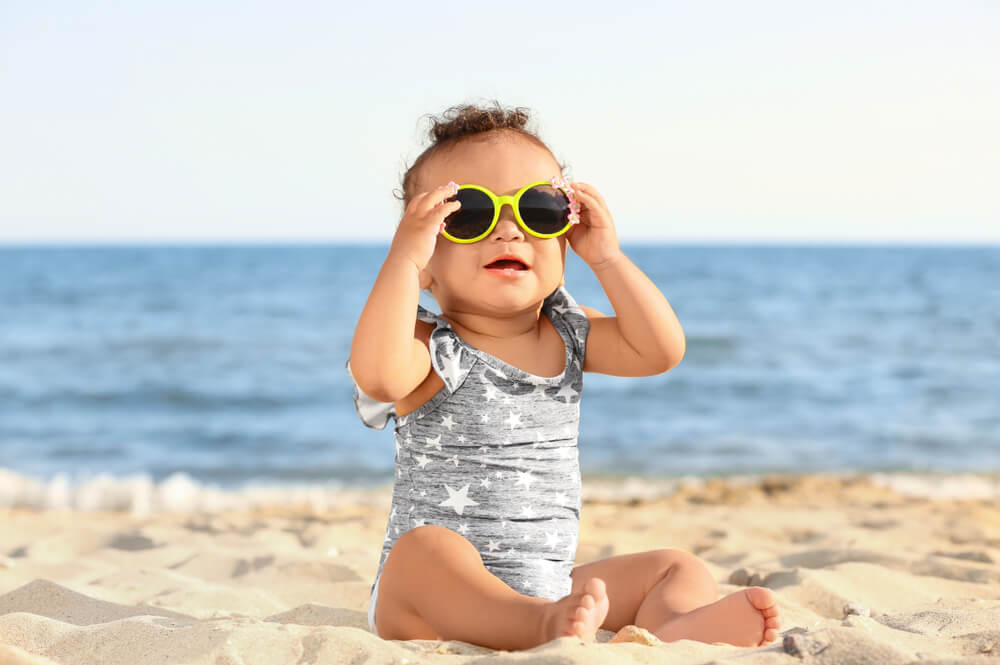 Little girl with sunglasses on beach at resort