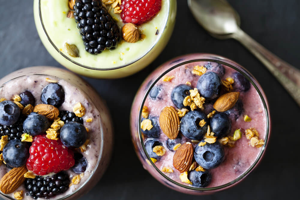 top view of 3 smoothies topped with berries and nuts
