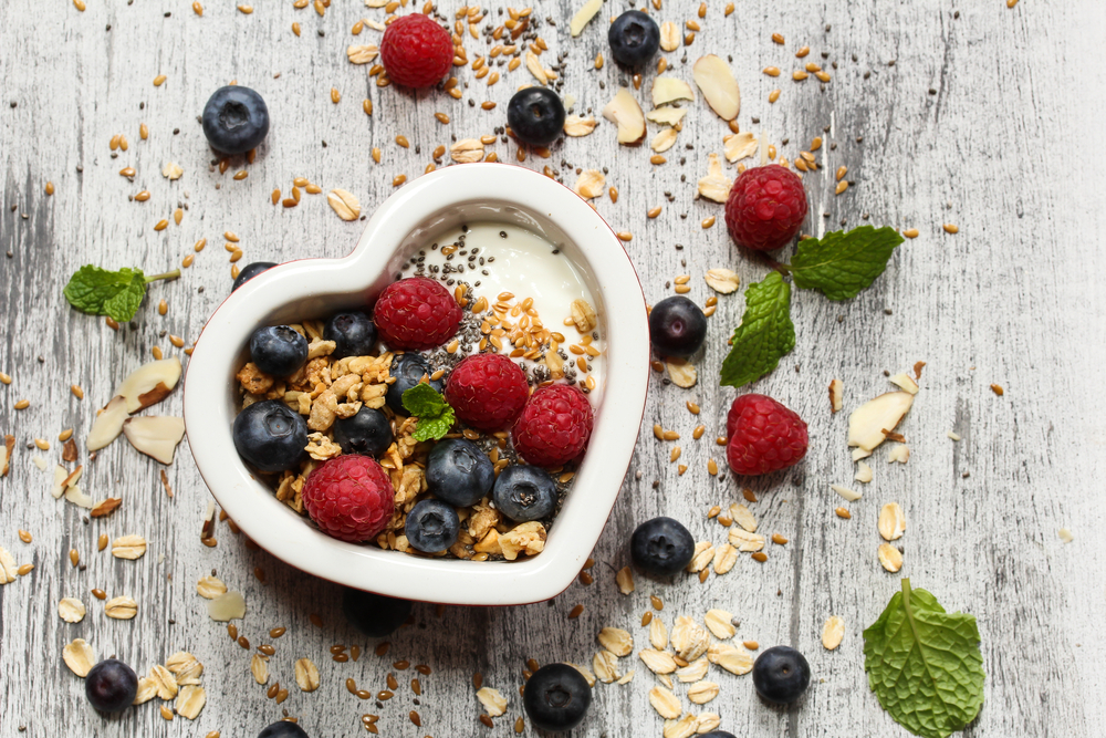breakfast Muesli in heart shaped bowl with blueberries raspberries granola chia seeds