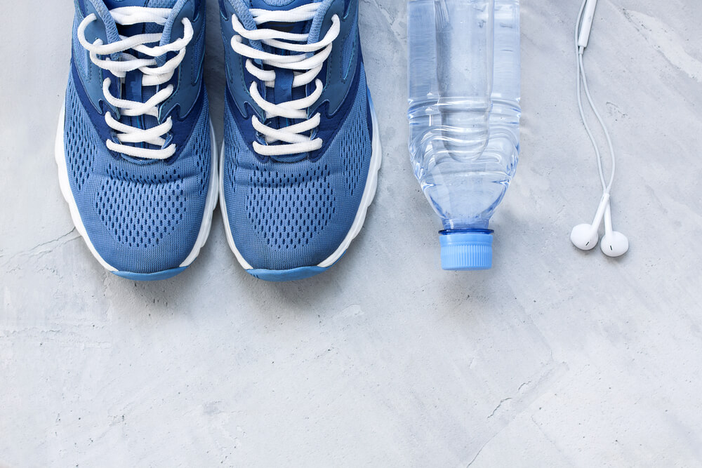 Flat lay sport shoes, bottle of water and earphones on gray concrete background. Concept healthy lifestyle, sport and diet. Focus is only on the sneakers.