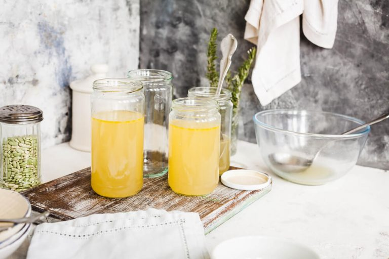 Bone broth soup in glass storage jars over stone kitchen table