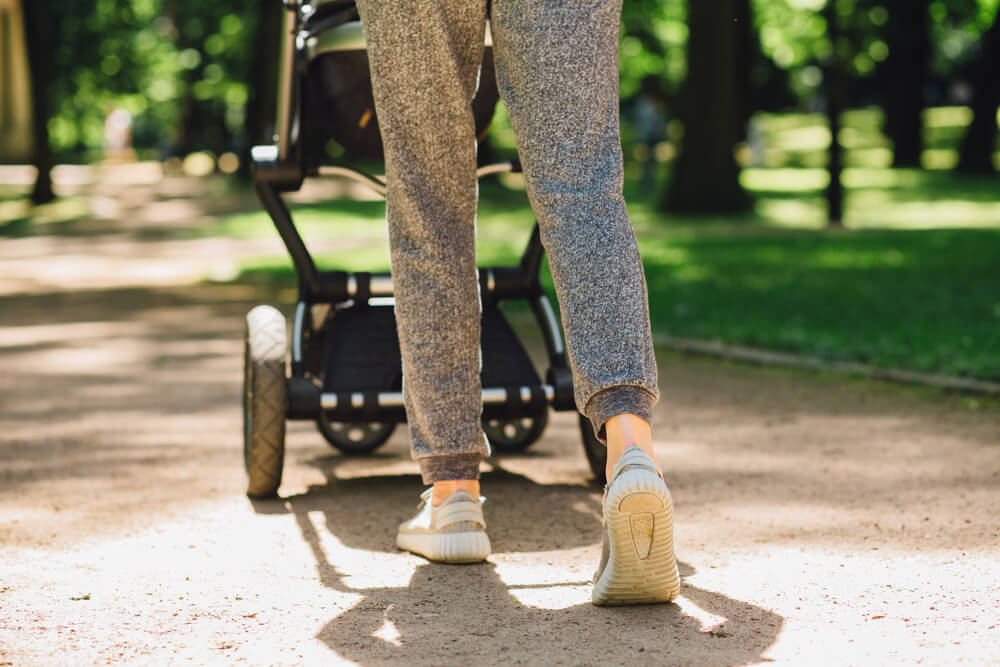Young mother exercises in a park. Wears gray sport shoes, pushes a stroller.