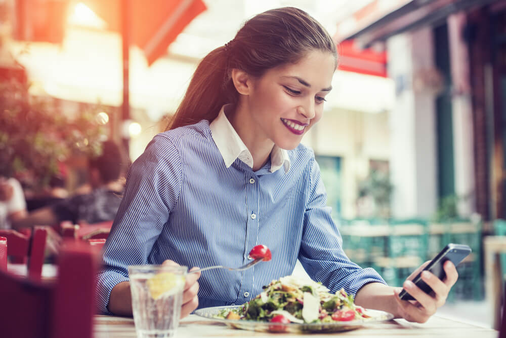 woman eating and texting