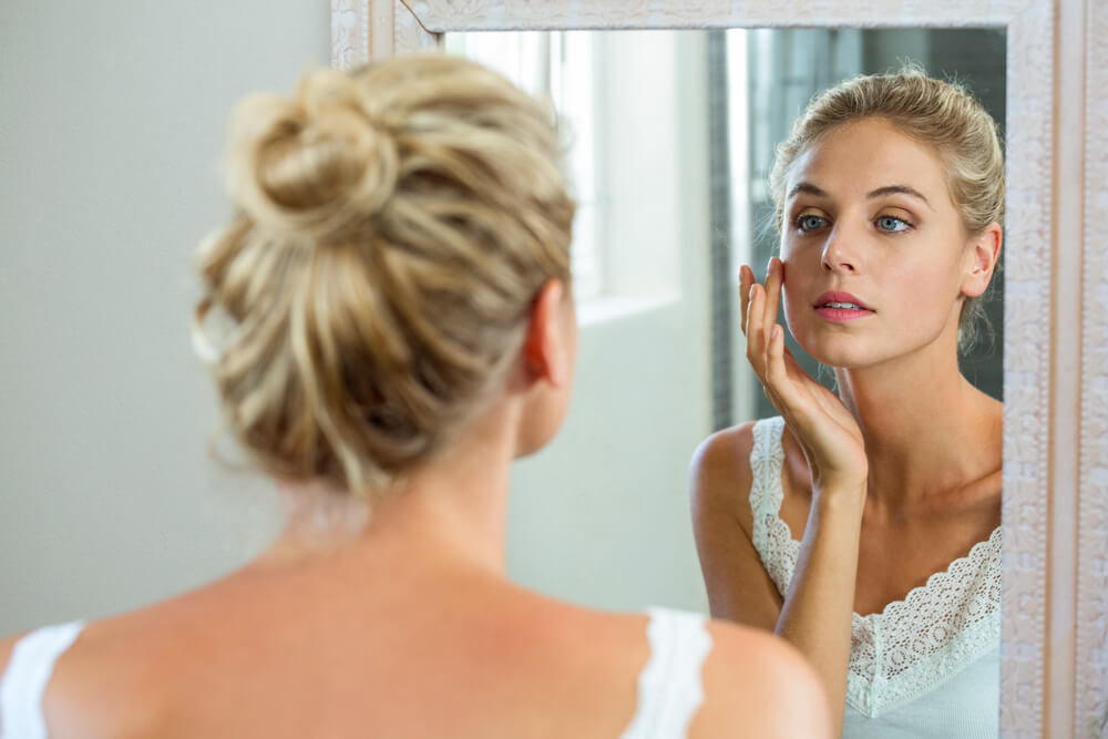 woman checking her skin in bathroom mirror