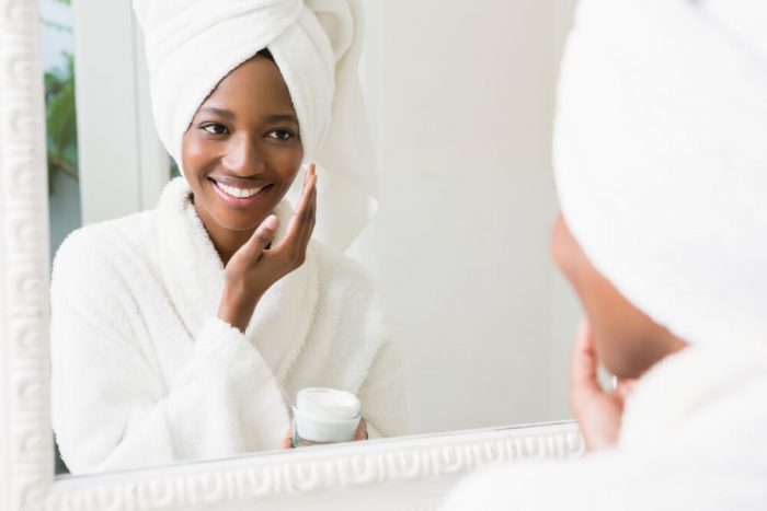 woman with glowy skin applying moisturizing
