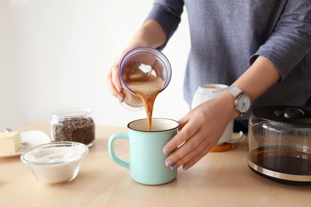 Image of someone pouring bulletproof coffee into a mug