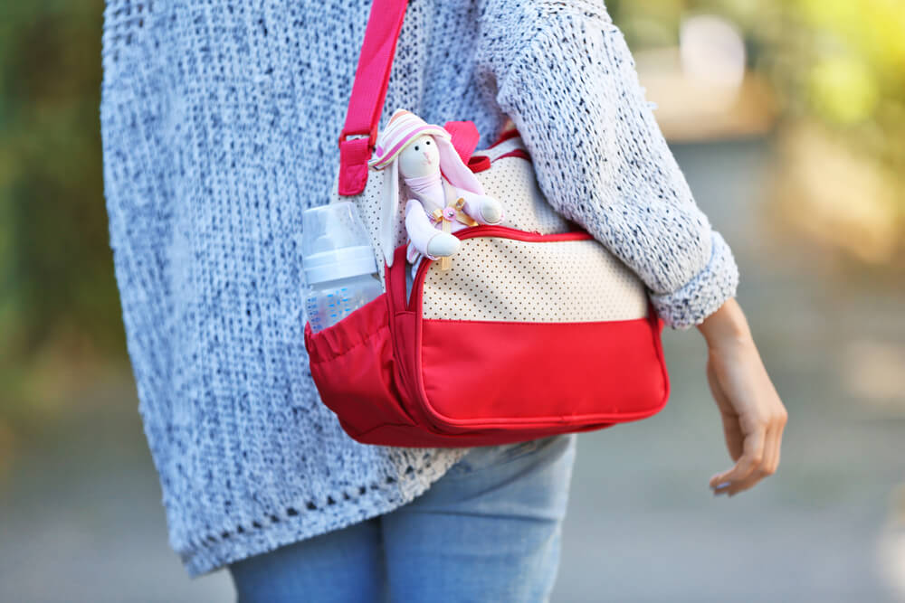 Photograph of woman holding a red and white diaper bag