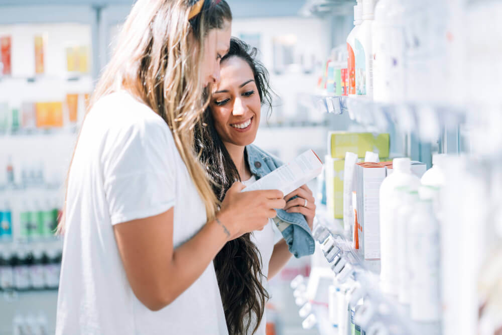 Image of two girls looking at sunscreen products in a store.