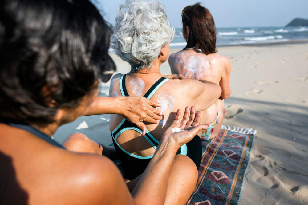 Photograph of three women applying sunscreen at the beach