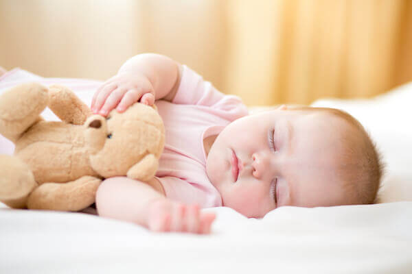 baby in pink onesie sleeping and holding teddy bear