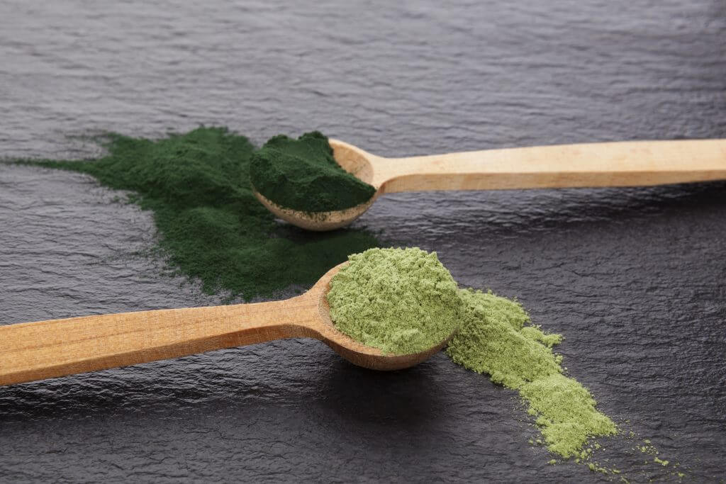 Two spoons with different green powders