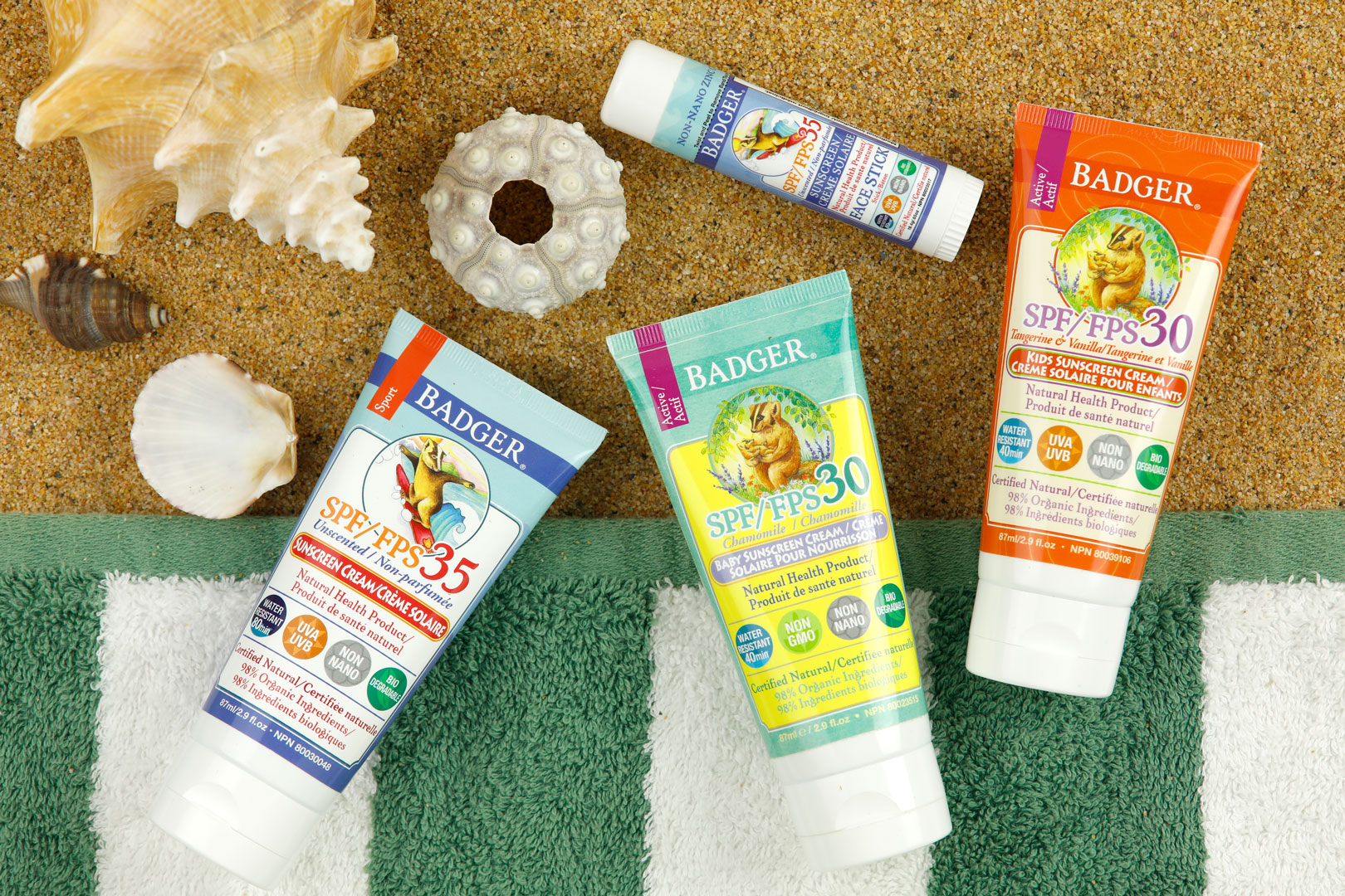 Four suncreen products on a green and brown background