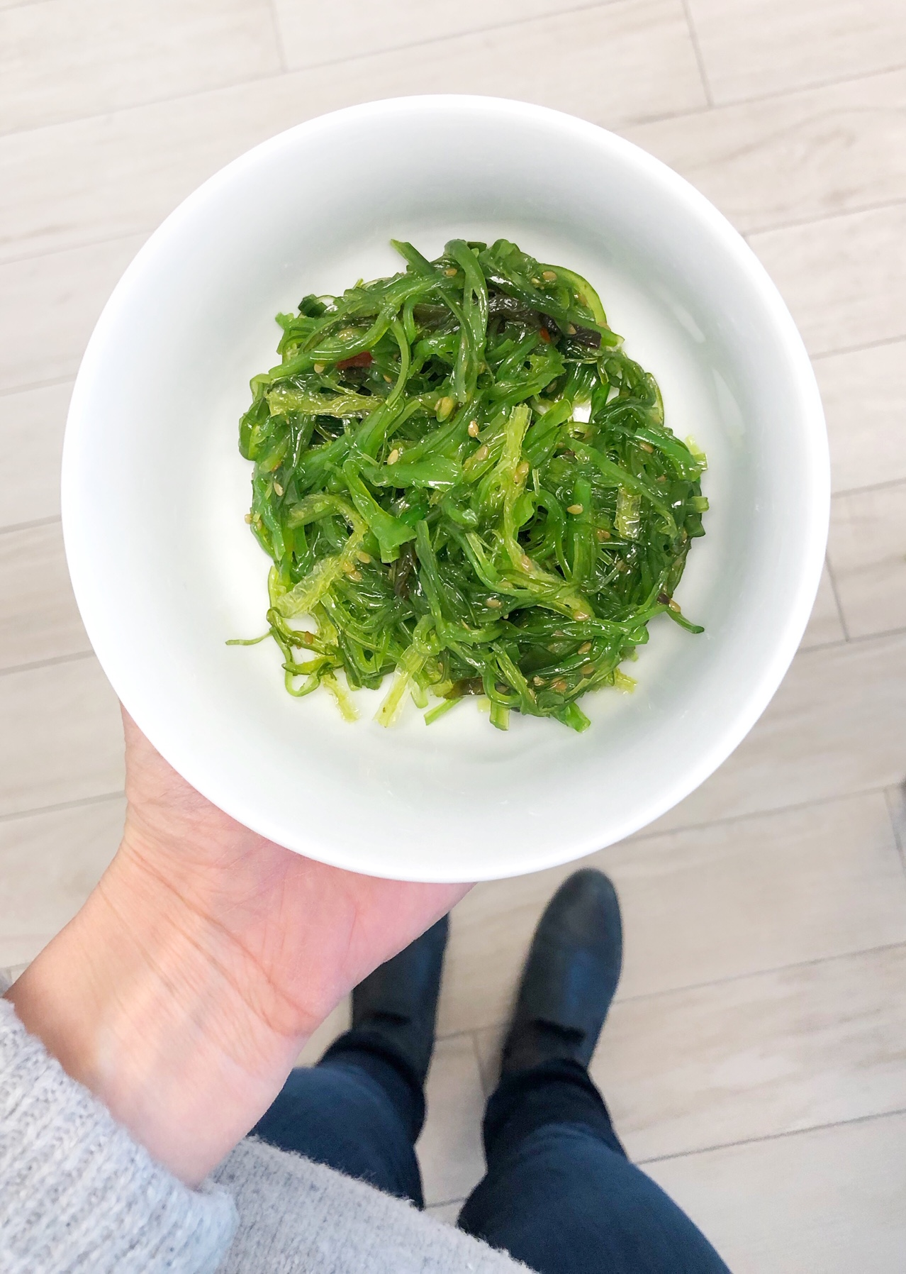 Person holding bowl of seaweed