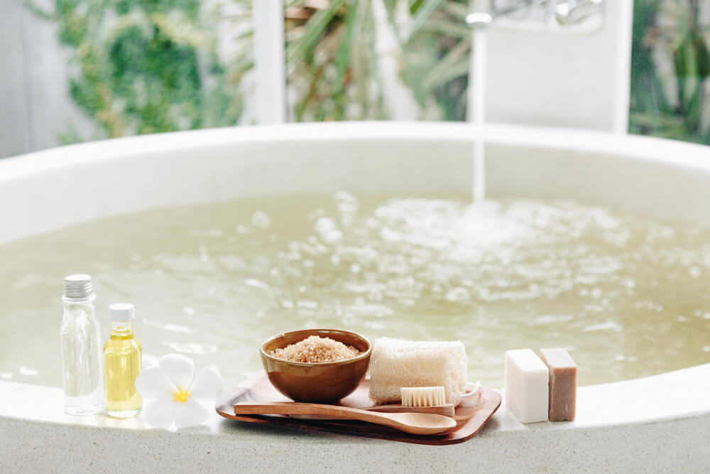 Bath with oils, soaps, and bath salts on the edge