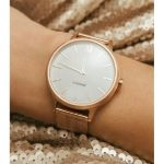 Image of rose gold watch with white face on a white person's wrist with gold sequin background