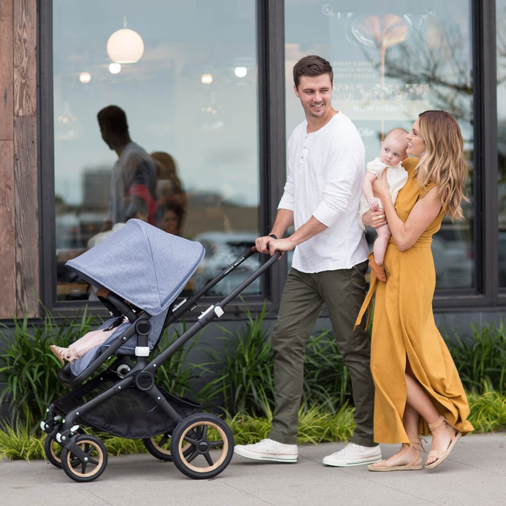 Couple pushing stroller and holding baby on a sidewalk on a sunny day