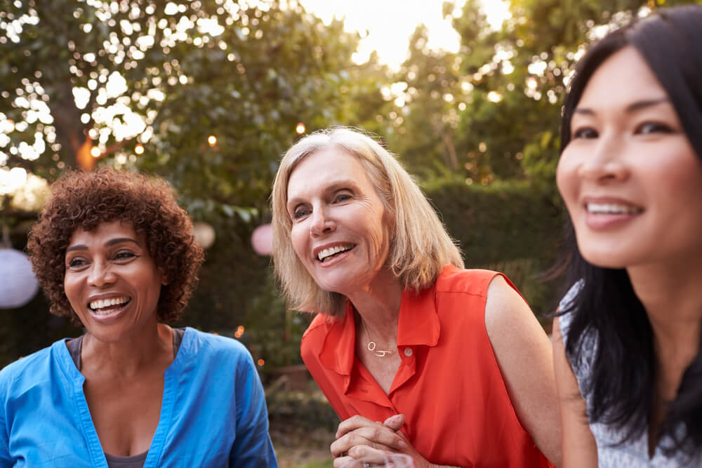 Three smiling women talk outdoors