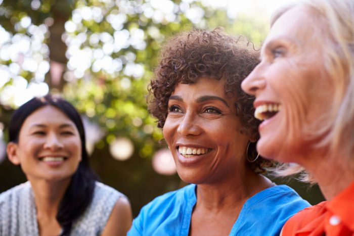 Three smiling women talk outside
